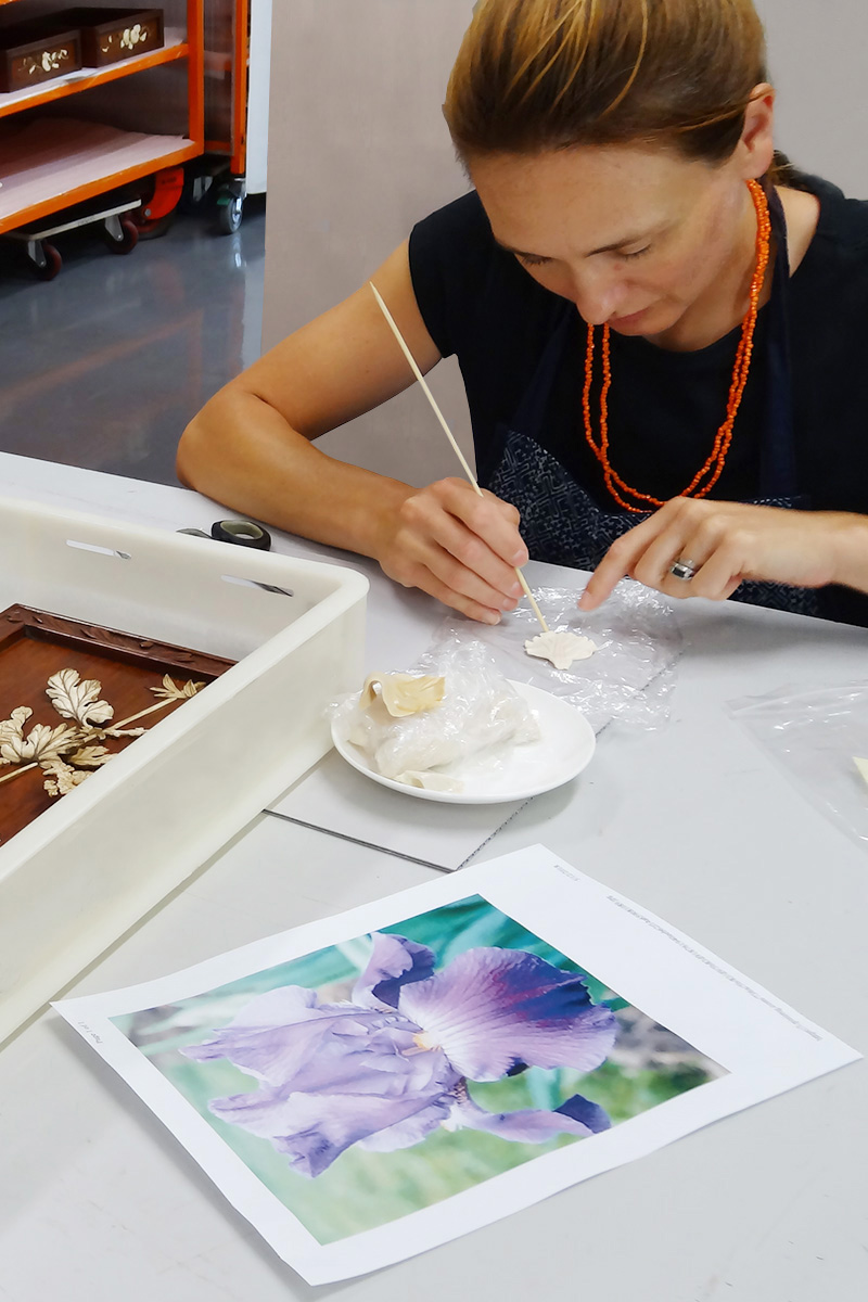 Photograph of conservator shaping new flower