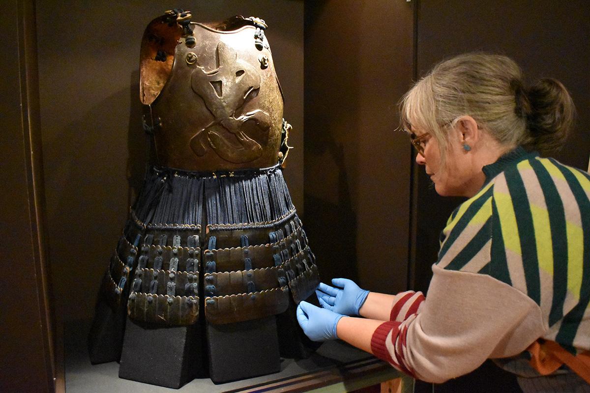Conservators installing cuirass in exhibition
