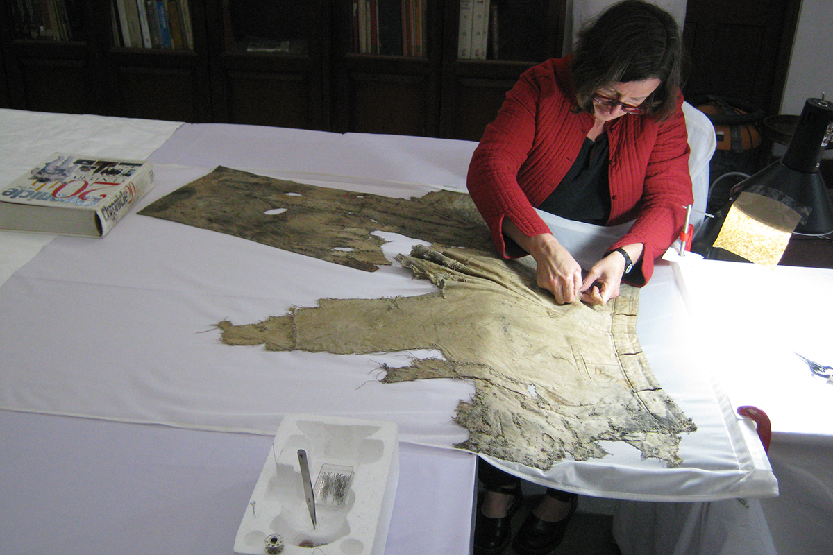 Conservator hand stitching trousers