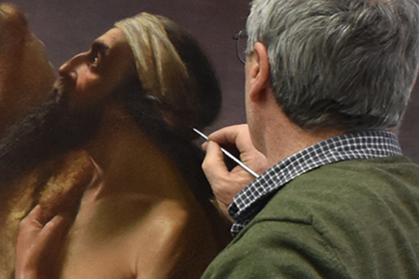 Conservator infilling painting