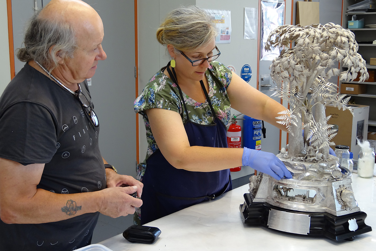 Silversmith and conservator reassembling silver trophy