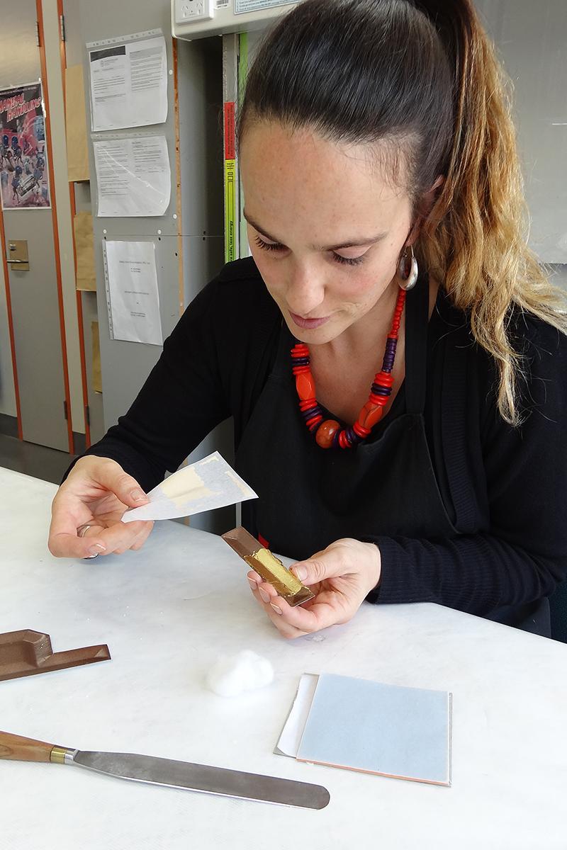 Conservator gilding letters