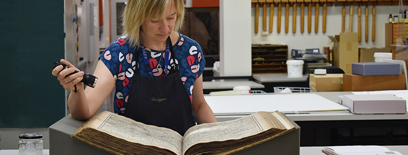 Conservator examining a book with a torch