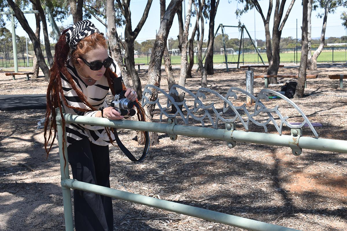 Conservator examining playground fence