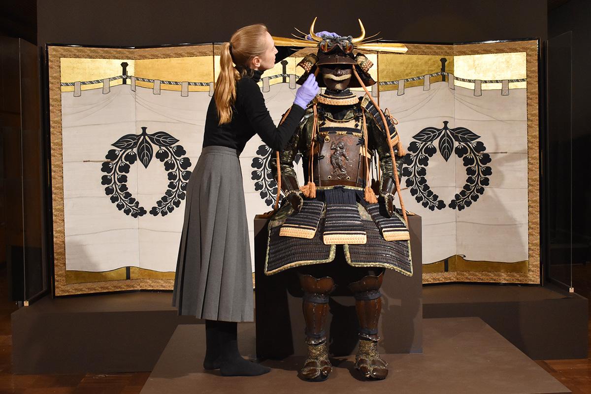 Conservators installing Samurai armour
