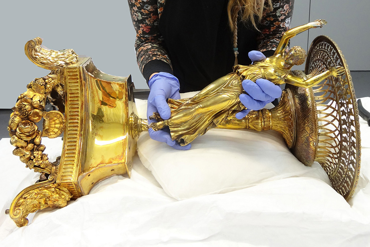 Conservator dissembling gilt silver stand