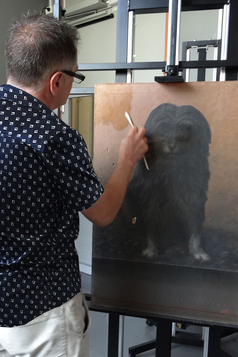 Conservator cleaning paintings