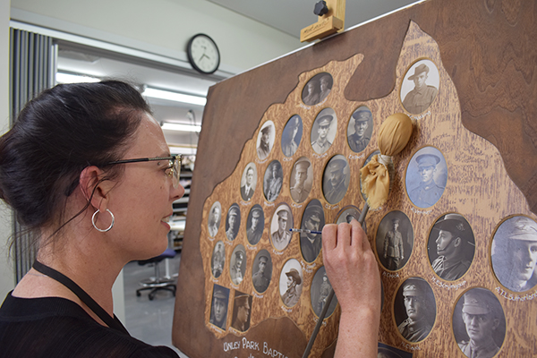 Conservator working on WW1 Honour Board