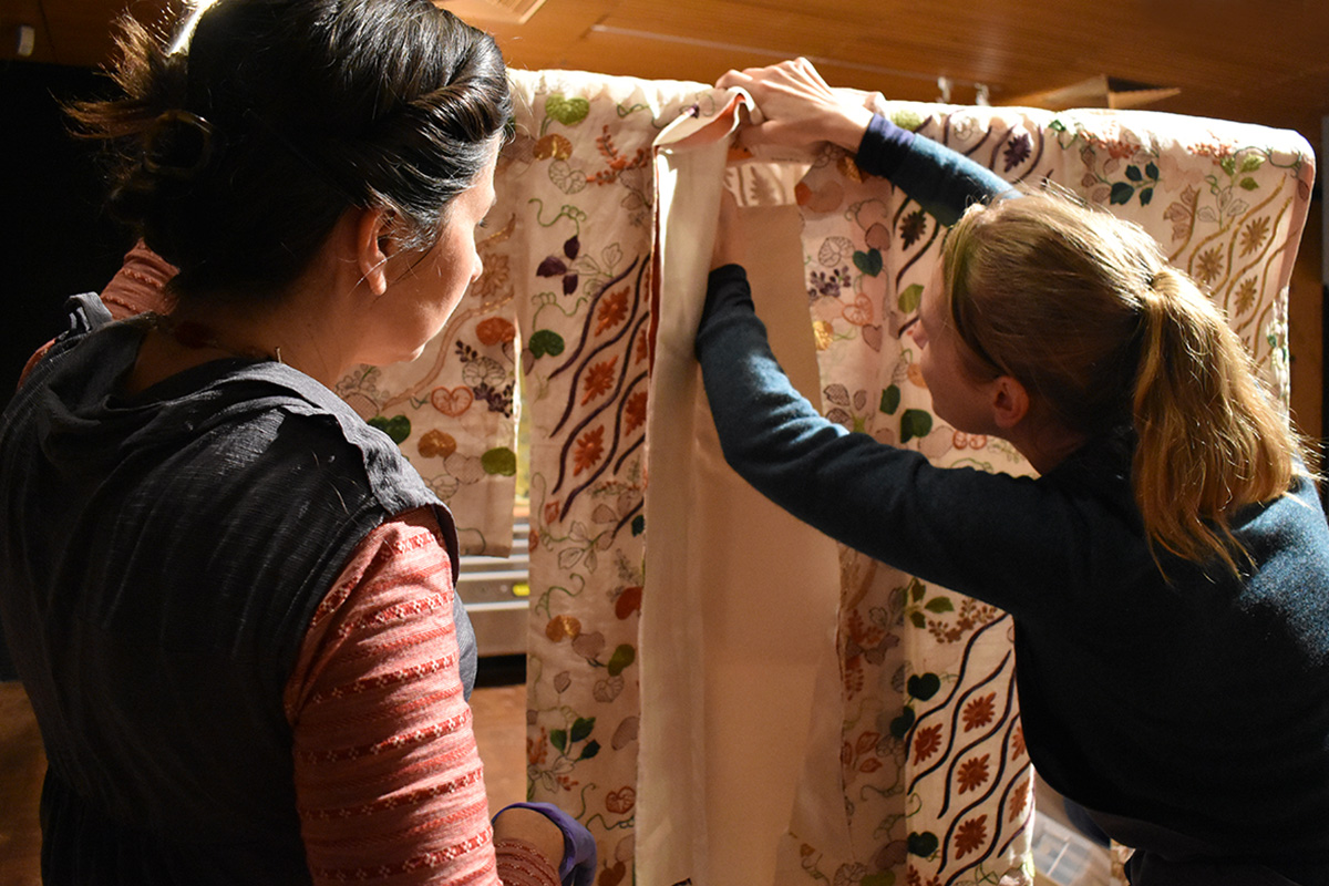 Conservators installing kimono in exhibition