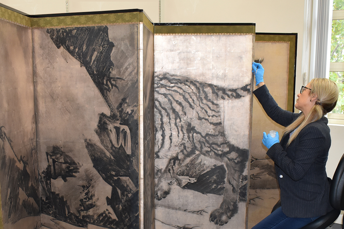 Paper conservator working on Japanese screen