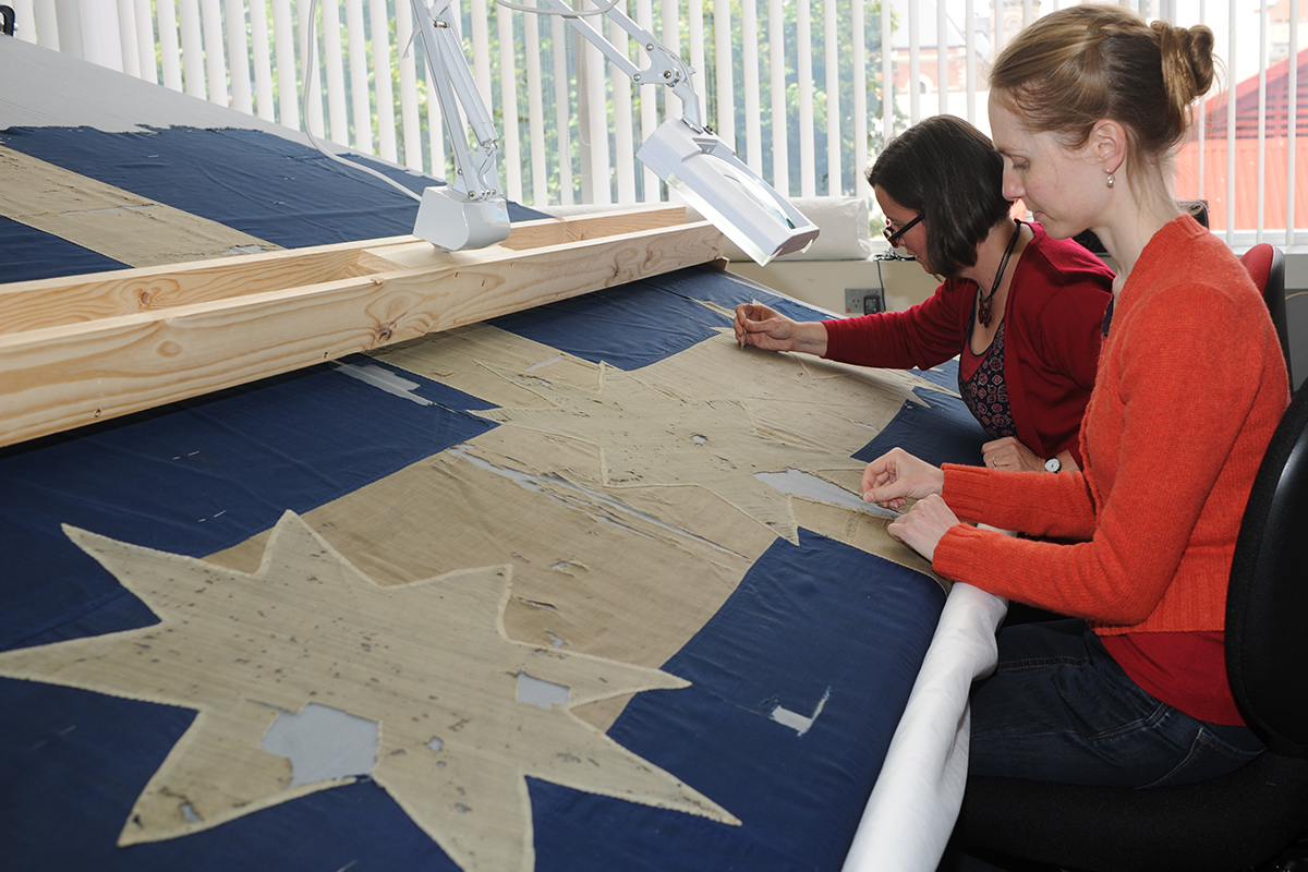 Conservators hand stitching Eureka flag