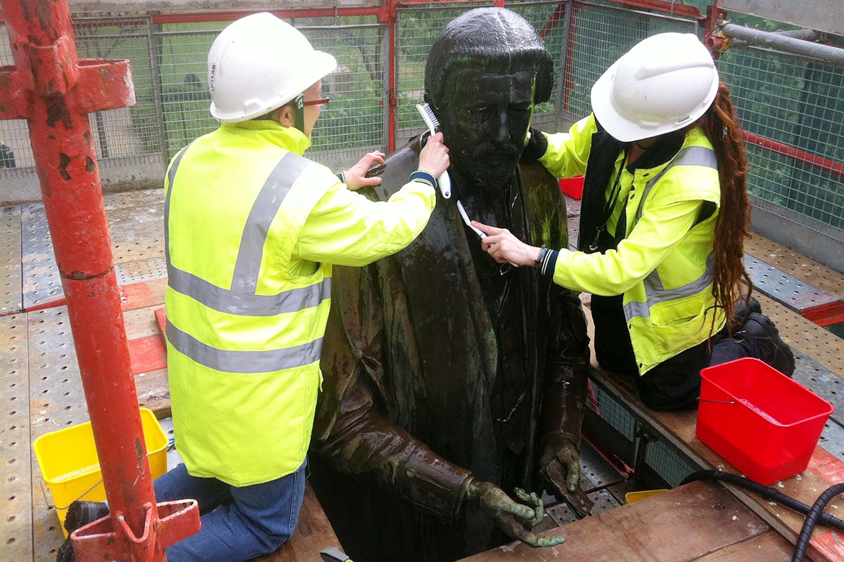 Conservators cleaning memorial