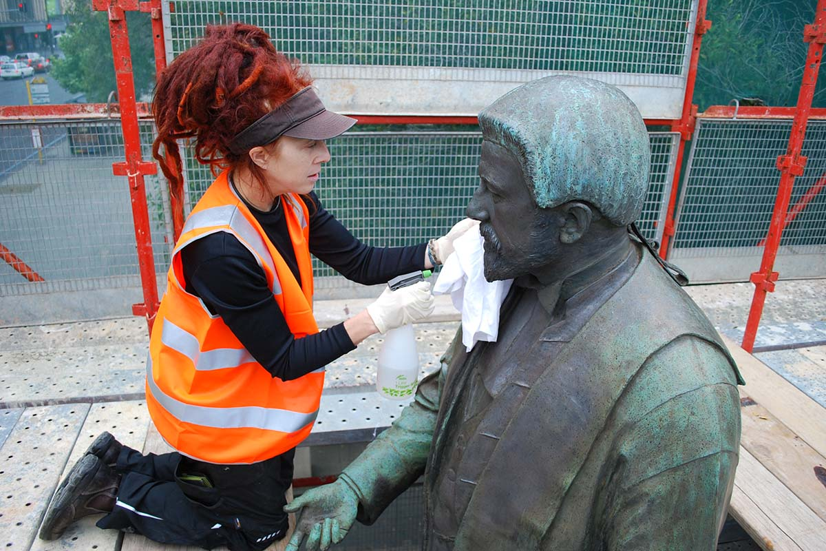 Conservator cleaning memorial