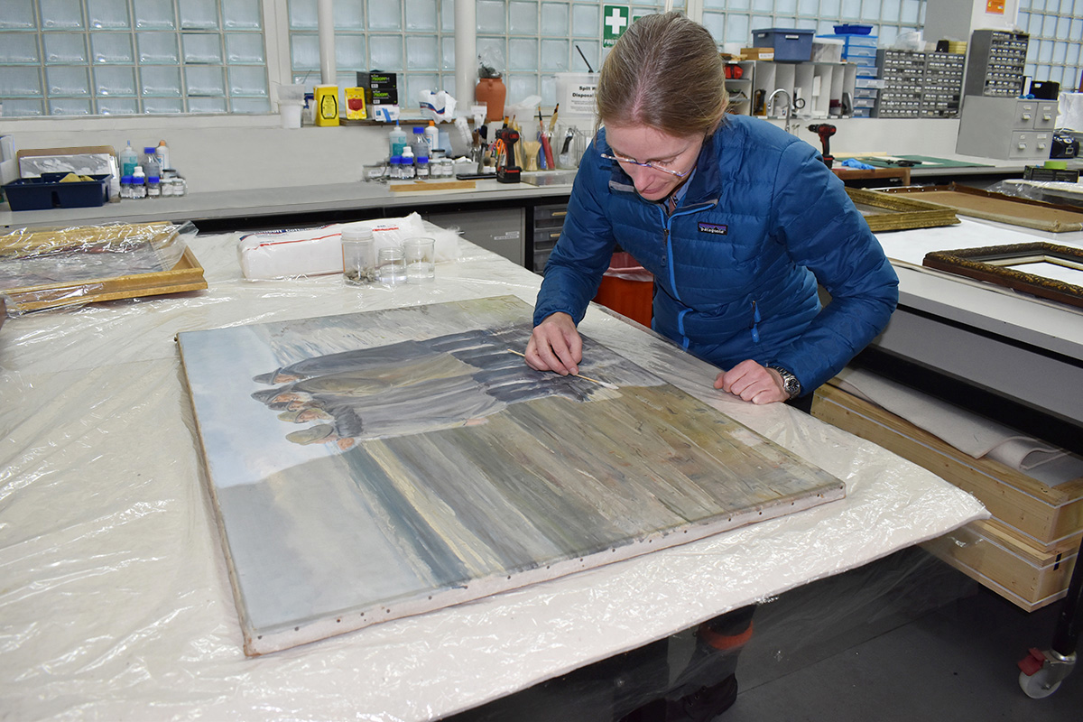 Conservator cleaning painting