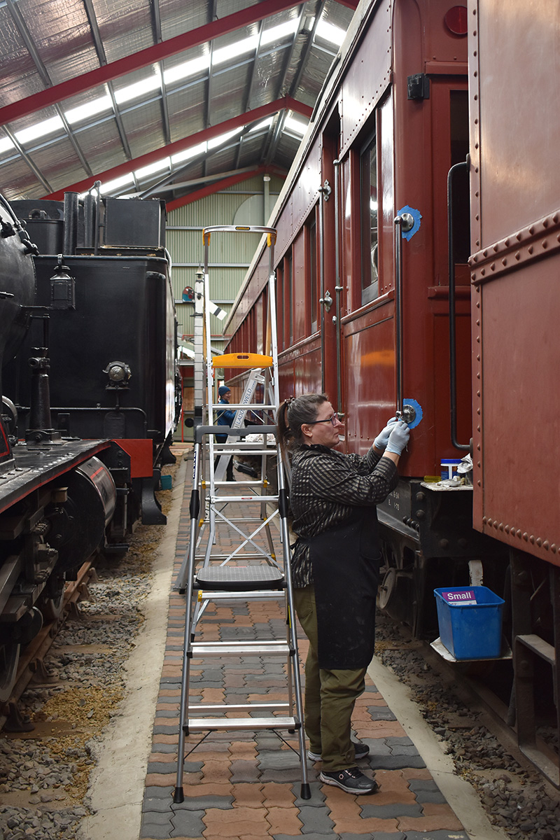Conservator cleaning railway carriage