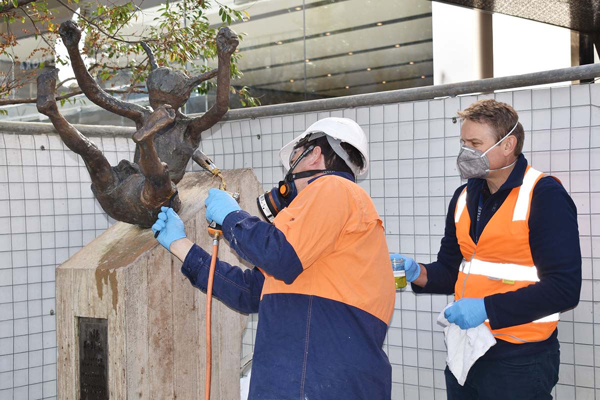 Conservator heating sculpture to clean surface