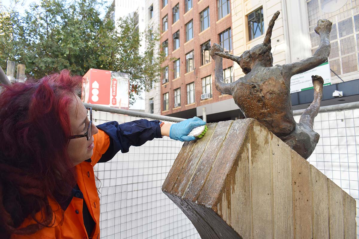 Conservator cleaning the plinth