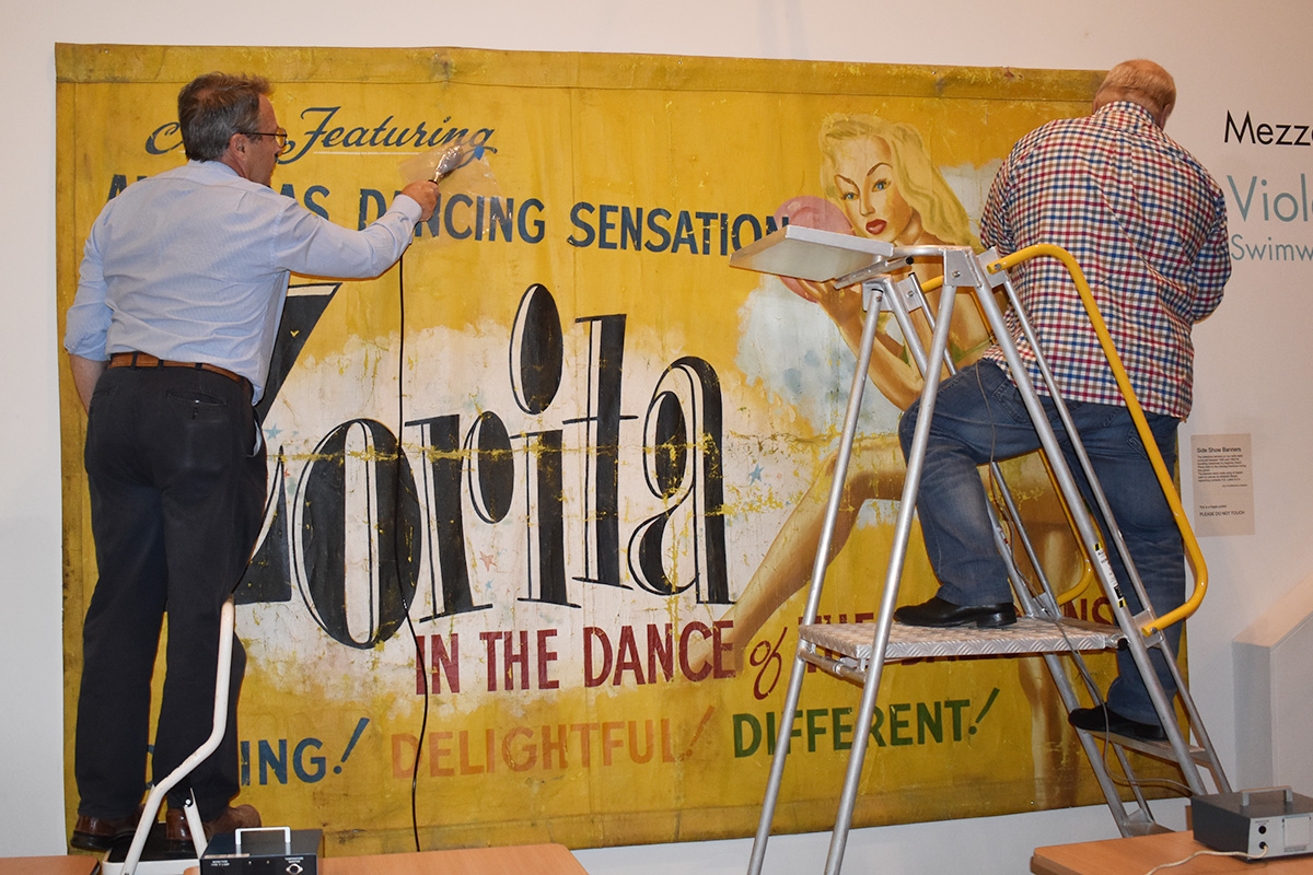 Conservators working on banner
